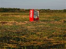 A vending machine, brought inland by a tsunami, is seen in a abandoned rice...