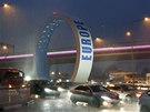 Cars drive through a flooded street near the airport during heavy rain in the...