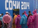 Builders stand in a line to enter a canteen in the Olympic Park in the Adler...