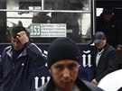Migrant workers exit a bus after being detained in a sweep by authorities at a...
