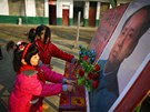 Students put plastic flowers next to a portrait of China's late chairman Mao...