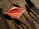 Students carry a Chinese flag during a ceremony at the Democracy Elementary and...