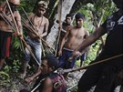 Munduruku Indian warriors stand guard over an illegal gold miner in western...