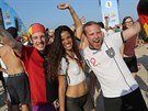 Soccer fans pose for a photo with a woman whose body is painted with Germany's...