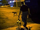 Bill leads his dog Paco, a Feist Terrier, though a vacant lot near trash...