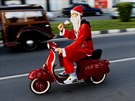 A man in a Santa Claus costume drives his Vespa during a parade at the  main coastal avenue in southern port city of Limassol, Cyprus, Sunday,  Dec. 14, 2014. Around 1000 people in Santa Claus costumes take part in  this parade during Christmas celebrations.