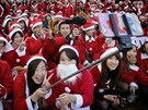 "People dressed in Santa costumes take ""selfies"" during the Tokyo Santa Run at..."