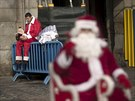 A man who performs for money wearing a Santa Claus outfit eats a sandwich as...