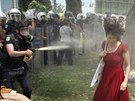 A Turkish riot policeman uses tear gas as people protest against...