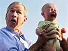 U.S. President George W. Bush hands back a crying baby that was handed to him...