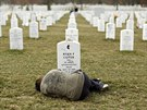 Lesleigh Coyer, 25, of Saginaw, Michigan, lies down in front of the grave of...