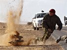 Rebel fighters jump away from shrapnel during heavy shelling by forces loyal...