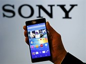 Employee poses with Sony's new Xperia Z4 smartphone after a news conference in...