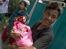 Buddha Tamang, 21 holds his one-day-old daughter at a makeshift shelter...
