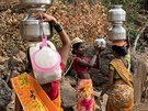 A woman helps another in carrying metal pitchers filled with water from a well...
