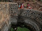 Bhaagi (L), third wife of Sakharam Bhagat, takes out water from a well as...