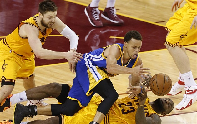 Stephen Curry z Golden State uniká, ležící LeBron James a Matthew Dellavedova z...