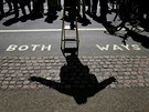 A speaker casts a shadow on the ground as he addresses a crowd at Speakers'...