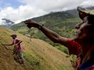 Coca farmer Alfredo Mosco, 44, right, instructs his young employee Donato...