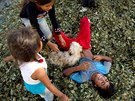 In this June 20, 2015 photo, kids play on a pile of coca leaves while helping...