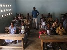 Teacher Kahon Rochel poses for a picture with students inside their classroom...