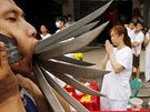 A devotee of the Chinese Bang Neow shrine with knives pierced through his...