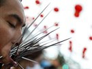 A devotee of the Chinese Bang Neow shrine with spikes pierced in his cheeks,...
