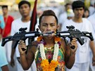 A devotee of the Chinese Ban Tha Rue shrine walks with guns pierced through...