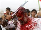Iraq Shi'ite Muslim men bleed as they gash their foreheads with swords and beat...