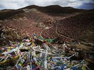 Tibetan prayer flags flutter above the Larung valley and its Larung Wuming...