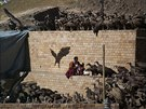 A Buddhist monk collects his belongings as vultures gather around a body of a...