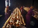 Tibetan Buddhist nuns keep yak butter lamps burning at a Buddhist laymen lodge...