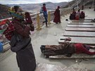 Ethnic Tibetan woman, carrying her baby on the back, prays at a monastery above...