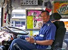 Plang Pansaior, a 66-year-old bus driver, waits for passengers while working...
