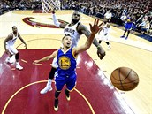 Za Stephenem Currym (30) z Golden State let� LeBron James z Clevelandu, o body ho p�ipravil kr�sn�m blokem.