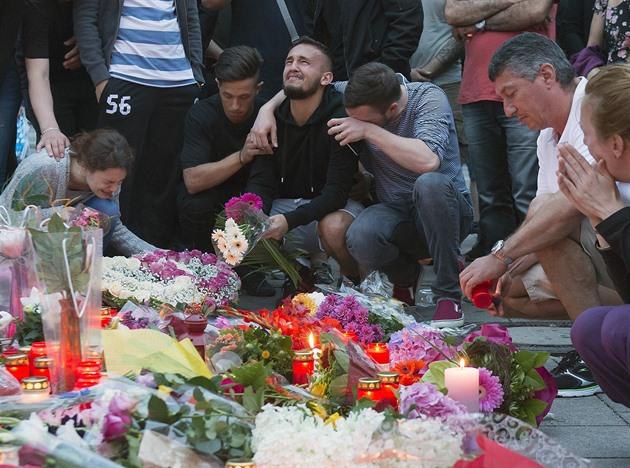 Lidé truchlí před nákupním centrem Olympia, kde mladý muž vzal život devíti...