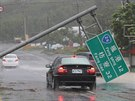 A car runs past a collapsed traffic sign, toppled by strong winds of typhoon...