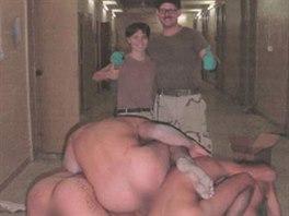 Lynndie Englandová a Charles Graner pózují s pyramidou tvořenou z nahých těl iráckých vězňů.