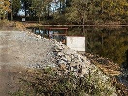Místo, kde se hráz rybníka Smyslov letos v květnu protrhla, je dobře viditelné díky navážce, kterou byla díra ucpaná.