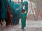 Girls stand in monsoon rains beside an open laundry in New Delhi