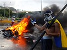 An opposition supporter stands next to a burning riot security force motorcycle...