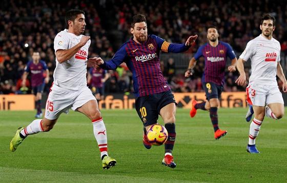 Barcelonskı útočník Lionel Messi vede míč (druhı zleva), napadá ho José Ángel...