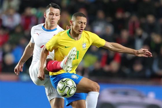 Reprezentační stoper Marek Suchı odkopává balon brazilskému útočníkovi...