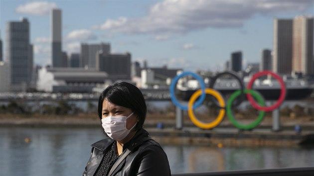 Turistka pózuje v Tokiu před olympijskımi kruhy s ochrannou rouškou na tváři.