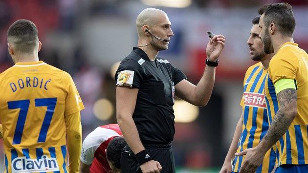 Rozhodčí Ondřej Ginzel ukazuje opavskım fotbalistům, že rozehrávat na Slavii budou až na pokyn píšťaly.