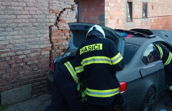 Vůz v Plotištích dostal smyk a skončil bokem ve zdi (26. 4. 2020).