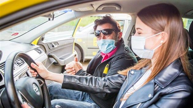Instruktor Václav Hess z Profiautoškoly ÚAMK i studentka Natálie Bohdalová musí mít v autě roušku.