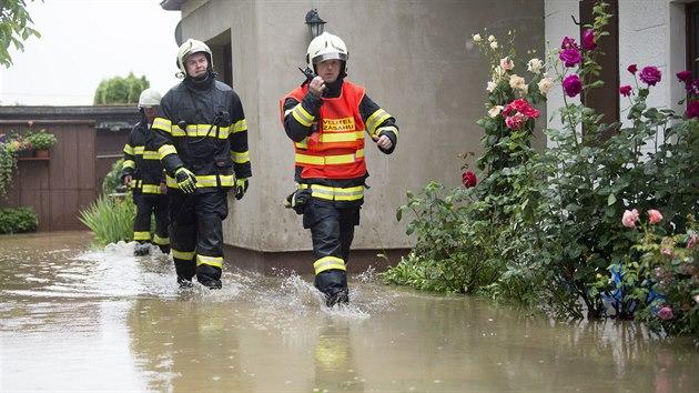 Hasiči u rodinného v Dolních Ředicích na Pardubicku, kde se kvůli silnım dešťům vylil z břehů Ředickı potok. (29. června 2020)