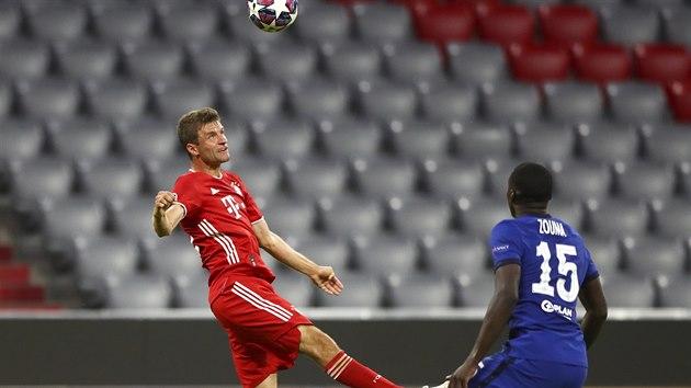 Thomas Müller (Bayern) se na natahuje za míčem, sleduje ho Kurt Zouma z Chelsea.