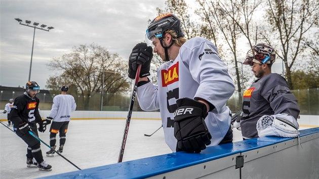 Vlevo Filip Chlapík, vedle něj brankář Michal Neuvirth. Pod mrakem bruslí na ledě v Dobříši.